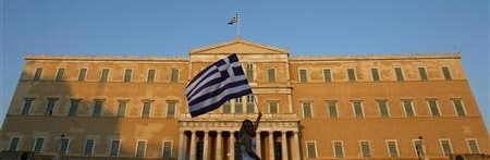 A woman raises a Greek flag during a rally against austerity in front of the parliament at Constitution square in Athens